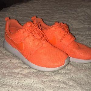 bright orange Nike Roshe runs